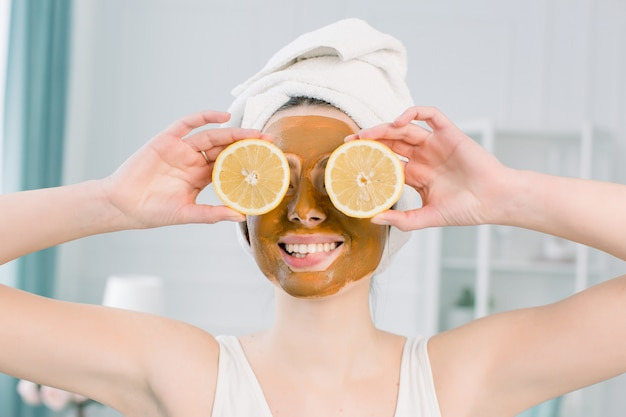 Эмоциональная молодая женщина в белом полотенце на голове и с лицевой маской и половинками спелого лимона на пустое пространство. фото женщины, получающей спа-процедуры. концепция ухода за красотой и кожей