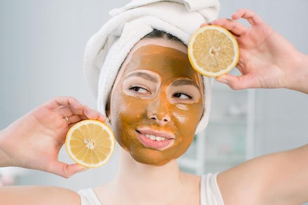 Смешная красивая модель держит кусочки лимона до ее глаз. фото девушки с увлажняющей коричневой лицевой маской. концепция ухода за красотой и кожей