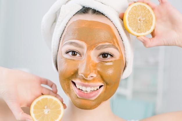 Красивая молодая женщина с лицевой маской грязи и половинками лимона на светлом пространстве в спа-центре