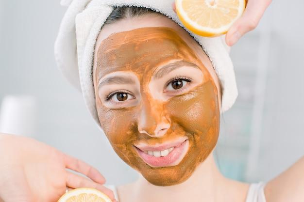 Милая, улыбающаяся девушка в белом полотенце и коричневой грязевой маске для лица с удовольствием с двумя половинками лимона, закрытый выстрел в пустое пространство