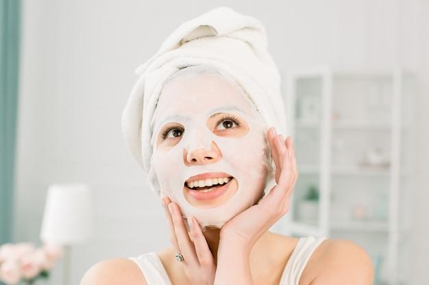 フェイスマスク、スキンケアの概念に適用する、頭に白いタオルを持つ若い美しい女性。スパ、ヘルスケア。彼女の顔に浄化マスクを持つ女性