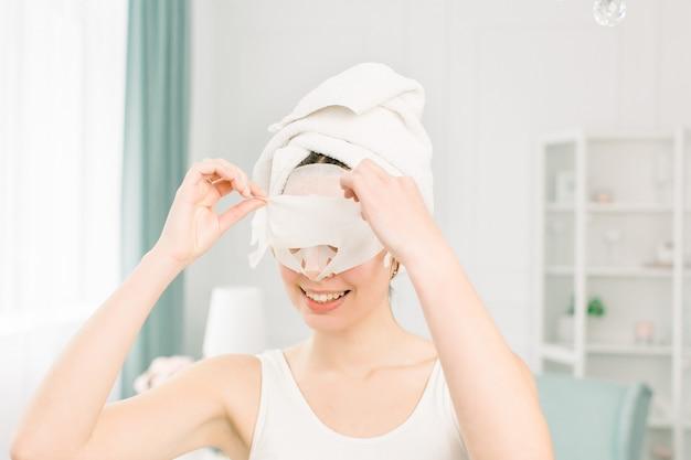 彼女の顔からマスクを引き離す顔の白いマスクを持つ白いタオルの少女。頭と肩、スタジオ、屋内の明るいスペース。化粧品の手順。美容スパと美容。