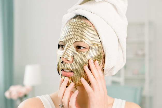 Косметическая процедура, портрет красивой женской модели с золотым продуктом лица на свежей коже. концепция ухода за кожей