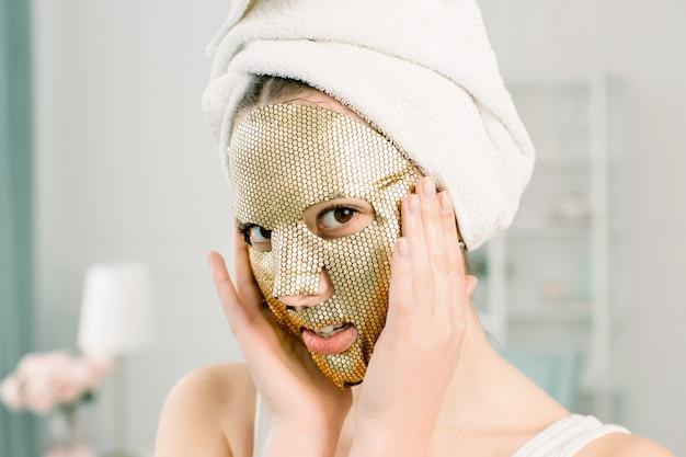 女性ゴールドシートマスク。カメラ目線の黄金の肌の化粧品で頭に白いタオルで美しい若い女性。美容スキンケアと治療