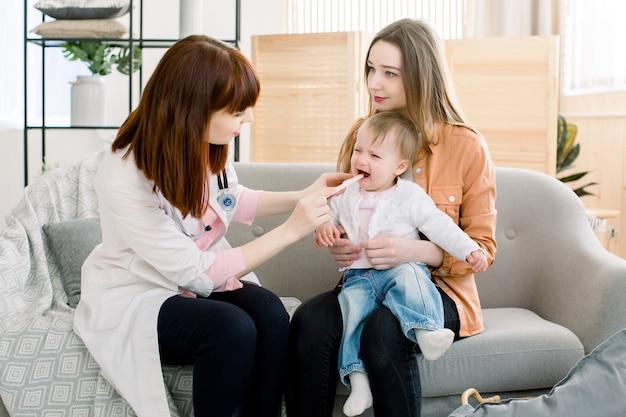 医学、医療、小児科のコンセプト-スティックで女医の患者の口を診療所で調べる白人の医者