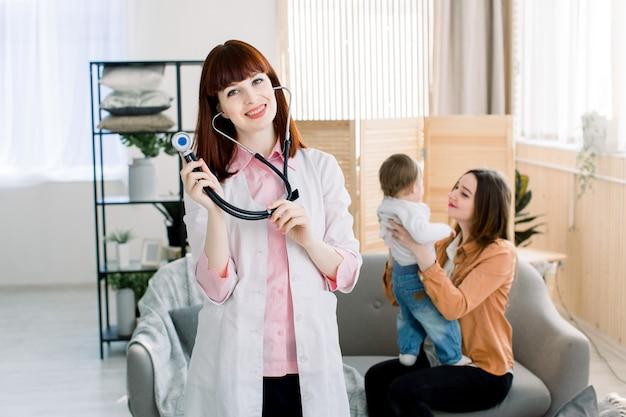 医師の診察で彼女の母親と一緒に小さな女の子。白い制服コートと聴診器で幸せな笑みを浮かべて女性若い医者