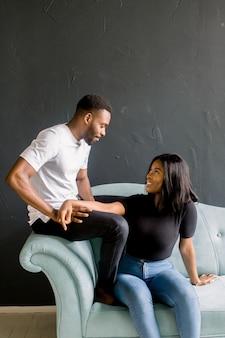 若い黒人男性と青いソファーに座っていた暗い背景にアフロアメリカンの女の子。若い男性と女性のスタジオでのファッションの肖像画