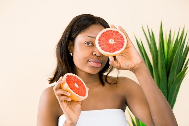 彼女の顔の前にグレープフルーツのスライスを保持している魅力的なアフリカの少女。白い背景で隔離のアフリカ系アメリカ人女性の笑顔の写真。美容スキンケアのコンセプト