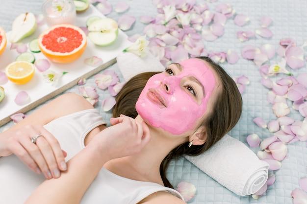 スパでのトリートメントやフェイスマスク、自然化粧品、彼女の周りの果物を作る若い健康な女性。藻のマスクを持つスパの若い女性。
