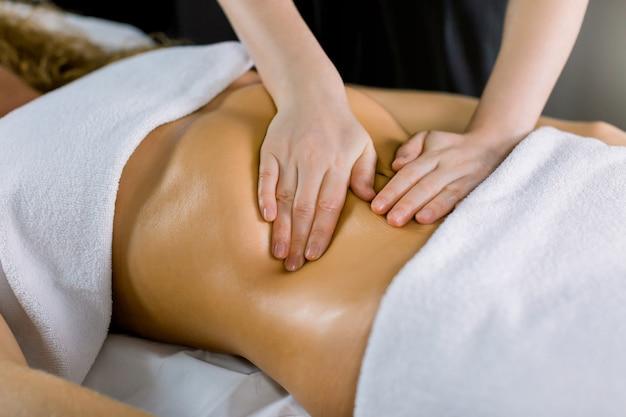 女性の腹部をマッサージしている手の拡大図。セラピストがお腹に圧力をかけます。医療スパセンターでマッサージを受ける女性