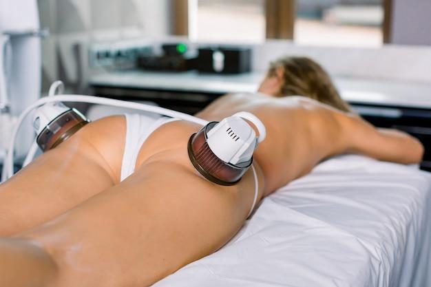 Вакуумный массаж тела. проблемные зоны в области бедер и ягодиц для похудения. крупный план ног молодой женщины на массажном столе