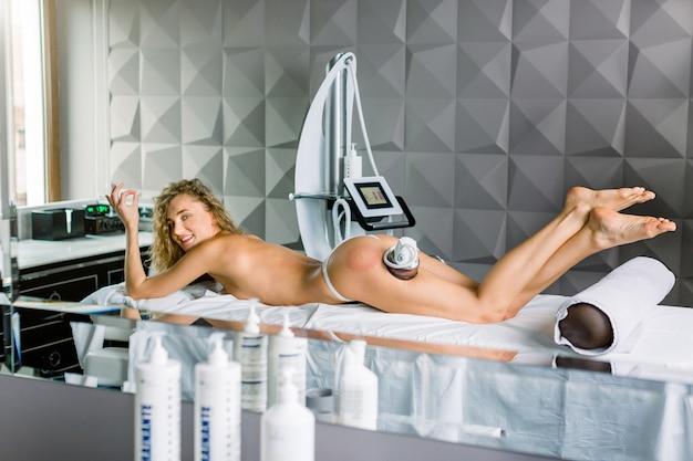 Вакуумный массаж и аппарат для похудения. антицеллюлитная коррекция фигуры. довольно молодая белокурая женщина лежа на кресле пока получающ вакуум и массаж ягодиц в салоне медицины