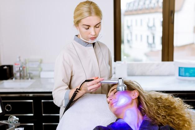 Врач-косметолог, занимающийся синей терапией, вел женскую терапию в салоне красоты, фототерапию для лица для очищения пор кожи. антивозрастные процедуры и процедуры фотоомоложения, крупным планом
