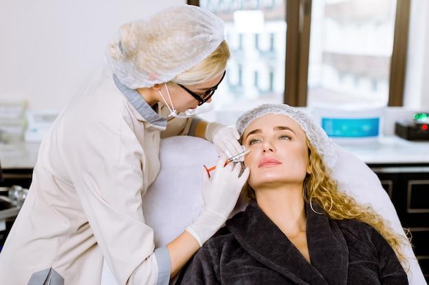 若い女性美容師は美しいブロンドの女性にクリニックでボトックス手順を実行します。美容学。