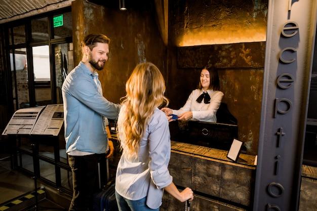 ホテルの女性受付と若いカップル。幸せなカップル、白人男性と女性、彼らのパスポートを示すホテルのフロントでチェックイン