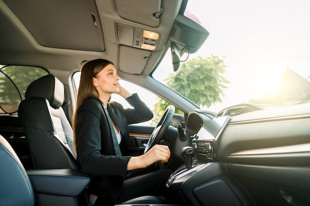 車のバックミラーを見て黒いスーツを着たジョージの若いビジネス女性。バックミラーで自分を探している若い笑顔実業家。側面図