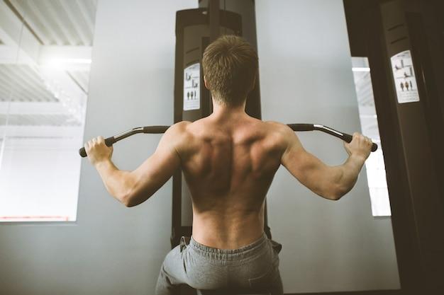 ハンサムなパワーアスレチック男トレーニング背中の筋肉をポンピングジムでプルアップします。強力なボディービルダーはジムでトレーニングし、背中をトレーニングします。筋肉トレーニングボディービルコンセプトをポンプ運動の男