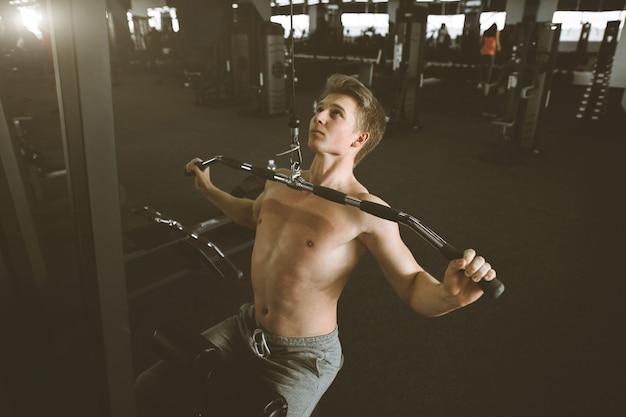 ハンサムなパワーアスレチック男トレーニング背中の筋肉をポンピングジムでプルアップします。強力なボディービルダーはジムでトレーニングし、背中をトレーニングします。