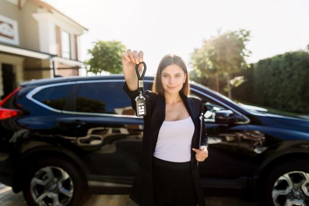 屋外の黒い車の前に立って、彼女の新しい車のキーを示す幸せな若い白人女性の写真。レンタカーと購入のコンセプト。キーに焦点を当てる