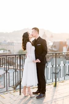 中国のかわいい新郎新婦の若い新婚カップルがキスし、結婚式の日に旧市街のテラスで抱きしめます。