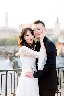 若い美しいアジアの新郎新婦、古いヨーロッパの都市の日没で幸せなカップル。