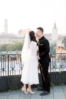 若い、魅力的なアジアのカップルの結婚式の肖像画。背の高い男が旧市街のテラスで妻の笑顔とキスをしている。