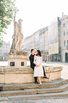 中国のかわいい新郎新婦の若い新婚夫婦は結婚式の日に旧市街の通りの石の階段でポーズをとってちょうど結婚しました。