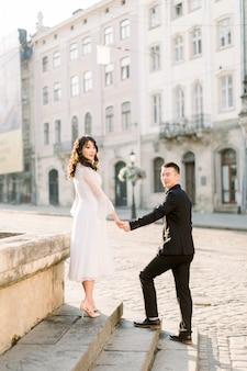 美しいスタイリッシュなアジア人カップルの男性と女性の古いヨーロッパの都市の夏の通りを歩いて