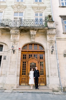 古いヨーロッパの都市の古い歴史的な建物のアンティークの茶色のドアに近いポーズ美しい中国のカップル