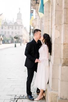 素敵な結婚式のカップル、アジアの男性と女性が旧市街でキスします。