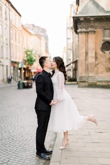 素敵なアジアのカップルが歩いて、街でキスします。男は黒の高級スーツ、白のスタイリッシュなドレスを着た女性