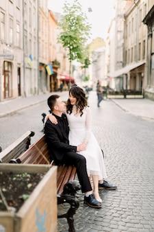 陽気な中国の結婚式のカップルは、屋外の旧市街中心部の通りのベンチに座っている間手を繋いでいます。