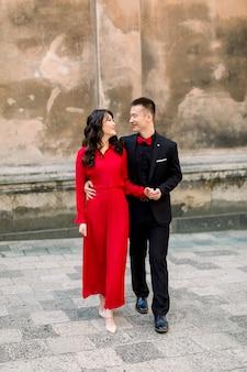 旧市街の背景にある新郎新婦の幸せで素敵なアジアカップル。