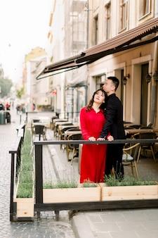 一緒にいて幸せ。旧市街中心部のサイドウォークカフェでポーズをとってエレガントな服で魅力的な中国のカップル。