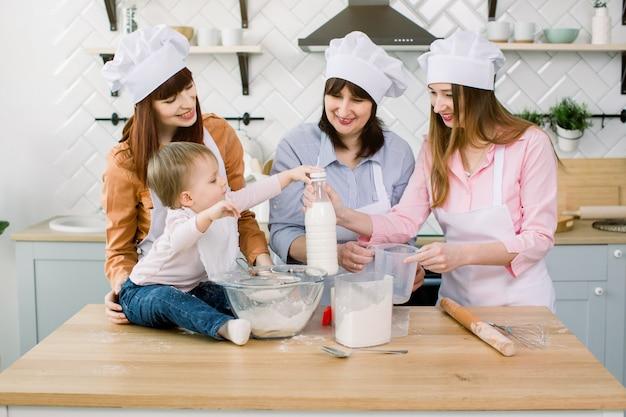 小さな赤ちゃんがお母さん、おばさん、おばあさんが生地をこねてパンを作るのを手伝っています。小さな女の赤ちゃんが牛乳を開きます。家族料理、母の日、一緒に焼く