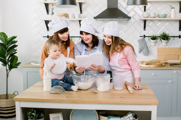 Привлекательные молодые женщины, женщина средних лет и маленькая милая дочь готовят на кухне. весело вместе, делая пироги и печенье. женщины читают кулинарную книгу с рецептами