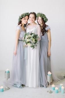 豪華な白いドレスを着たかわいい花嫁がウェディングブーケを保持し、灰色のドレスと花輪を着た彼女のブライドメイドと一緒に立っています。