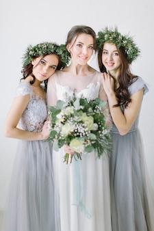 ブルーグレーのドレスと花輪の花嫁介添人と花束を保持している白いウェディングドレスで美しい笑う花嫁