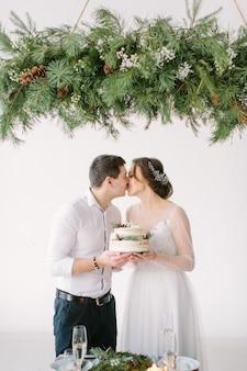 Жених и невеста целуются за столом в банкетном зале ресторана и держат свадебный торт, украшенный ягодами и хлопком