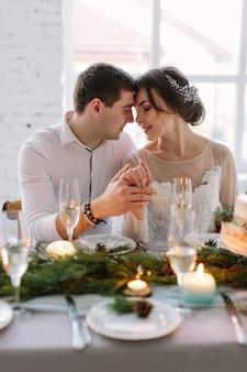 Жених и невеста позируют на украшенном банкетном столе в белом зале
