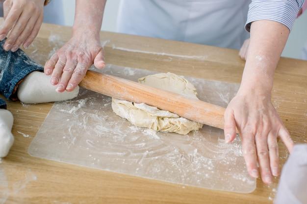 生地をシーティング。女性の手はめん棒を握り、打ち粉にされています。めん棒で生地を焼く手。キッチンで焼く。職場のシェフ。台所の女性、テーブルの上の赤ちゃんの小さな足
