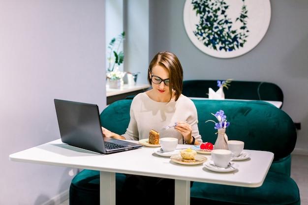 Мягкий фокус выстрел женщины в коворкинг пространстве или кафе с подключением к интернету, работать на ноутбуке и наслаждаться десертами, ожидая клиентов. сосредоточены на работе.
