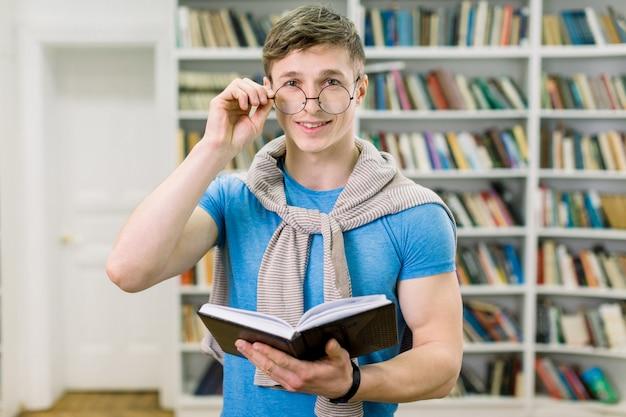 試験の準備。陽気な魅力的な若い白人男、彼の眼鏡に触れる、本を読んで、笑顔