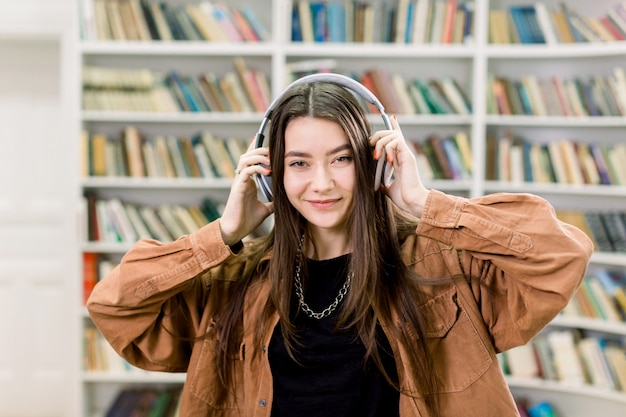 Довольно забавная улыбающаяся молодая девушка с длинными каштановыми волосами, слушающая список лучшей музыки в наушниках, держащая руки на голове и позирующая в библиотеке на пространстве больших книжных полок