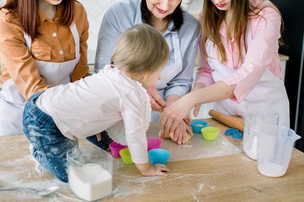 Счастливые женщины в белых фартуках выпечки вместе. фото конца-вверх рук женщин и маленького младенца подготавливая тесто для печь булочек. концепция семьи, кулинария, выпечка и люди