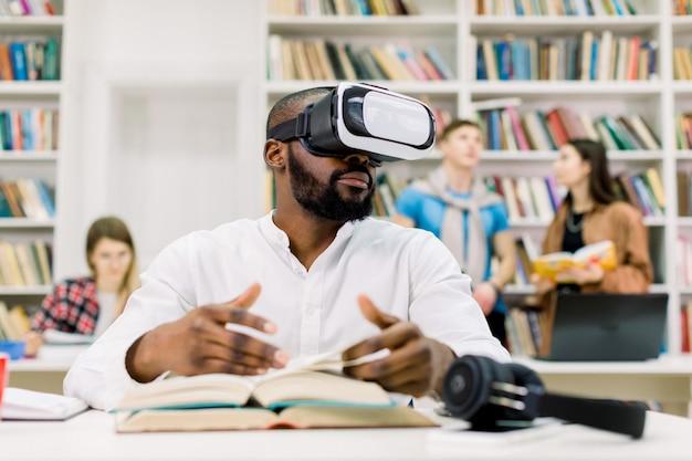 Молодой привлекательный африканский мужчина с бородой, одетый в повседневную белую рубашку, учится в библиотеке, использует очки виртуальной реальности гарнитуры, листая страницы книги