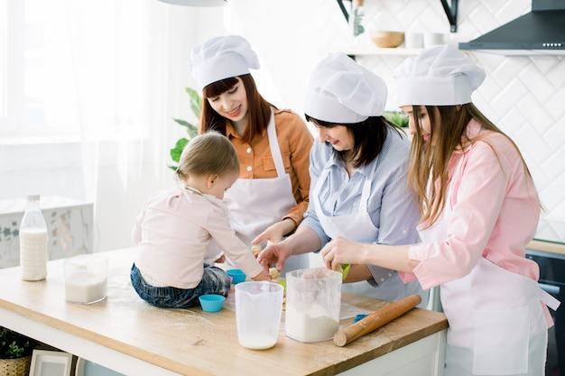 テーブルの上に座っているかわいい女の子と彼女の美しい母親、叔母、エプロンの祖母は、マフィンの生地を準備して、自宅のキッチンで焼きながら笑っています。母の日のコンセプト