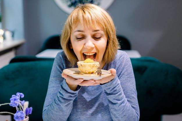 カフェで大きな喜びでケーキを食べる若いかなり笑顔の女性の肖像画。カフェでおいしいデザート。カフェでケーキを食べる女性のクローズアップ