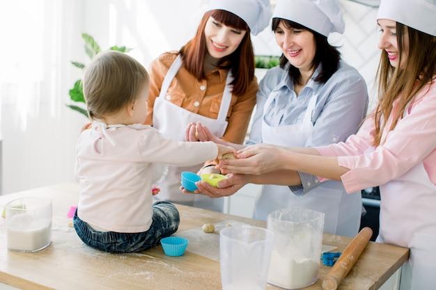 母の日、家族、料理、人々のコンセプト-かわいい赤ちゃんの女の子と彼女のお母さん、おばさん、祖母が家庭の台所でカップケーキを作り、飾る