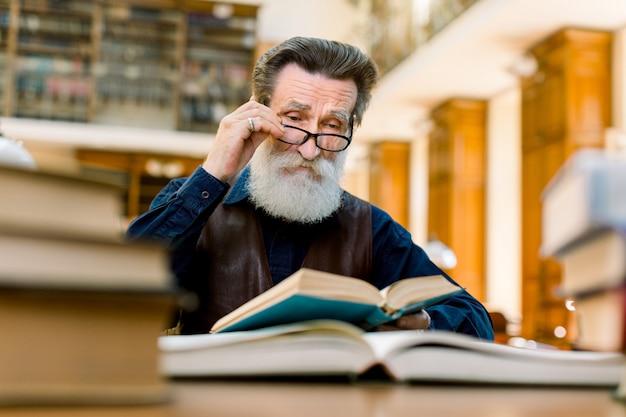 Пожилой профессор старика, писатель, читая книгу в старой винтажной библиотеке. умный старик в очках и стильной одежде читает книгу в библиотеке